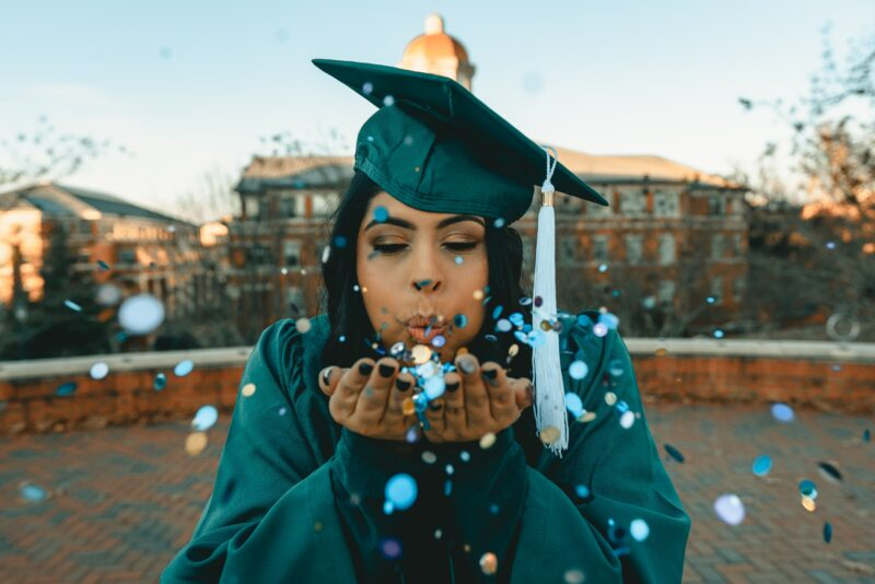 Graduating young woman blowing confetti from her hands