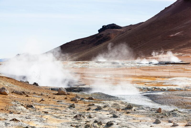 geothermal smoke coming from the ground against a mountain in Iceland